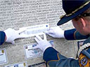 Etching a name from the wall of honor.